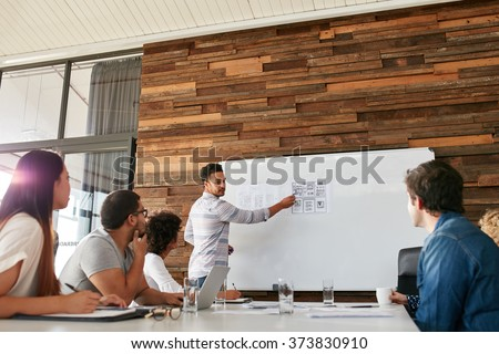 Portrait of young businessman giving presentation to colleagues. Young man showing new app design layout on white board to coworkers during business presentation. - stock photo
