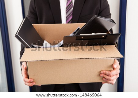 Portrait of young businessman holding cardboard in office - stock photo