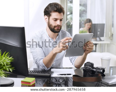 Portrait of young businessman holding digital tablet in his hands while sitting at office desk in front of computer and working. Young professional man touching the screen.