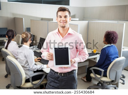 Portrait of young businessman holding tablet computer while colleagues working in background at call center - stock photo