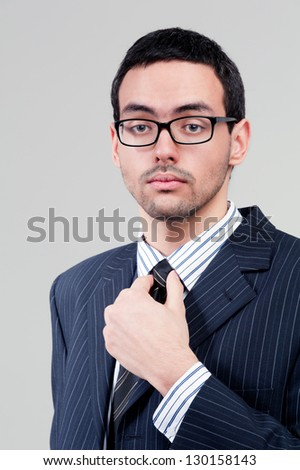 Portrait of young businessman holding the tie on the gray background