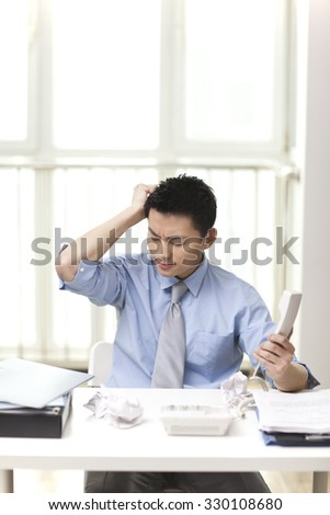 Portrait of young businessman holing phone in office - stock photo