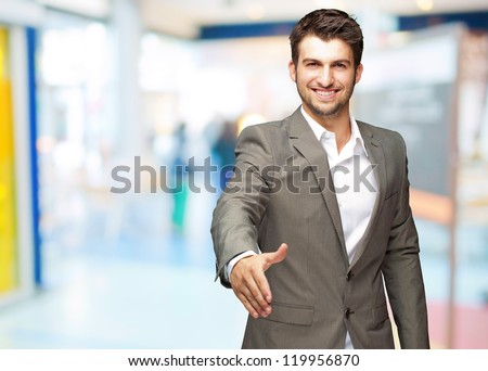 Portrait Of  Young Businessman In A Suit Holds Out His Hand For A Handshake, Indoor - stock photo