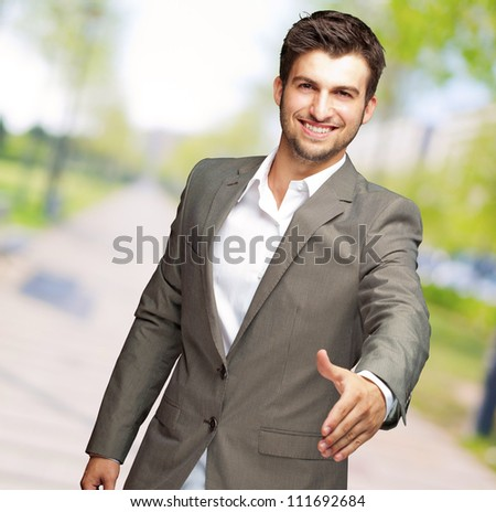 Portrait Of  Young Businessman In A Suit Holds Out His Hand For A Handshake, Outdoor - stock photo