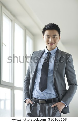 Portrait of young businessman in corridor - stock photo