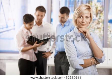 Portrait of young businessman in office, smiling. Colleagues talking in background. - stock photo