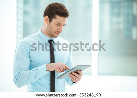 Portrait of young businessman in office with big window. Businessman using tablet computer - stock photo