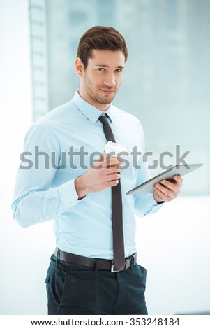 Portrait of young businessman in office with big window. Businessman using tablet computer, holding cup of coffee and looking at camera