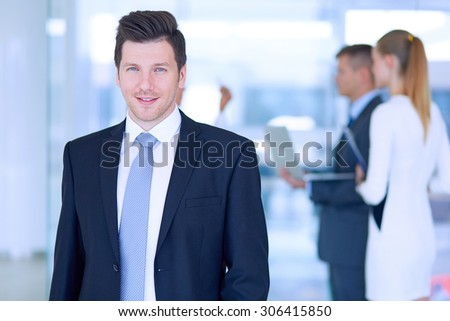 Portrait of young businessman in office with colleagues in the background . - stock photo