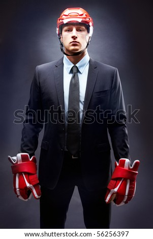 Portrait of young businessman in suit and hockey helmet and gloves - stock photo