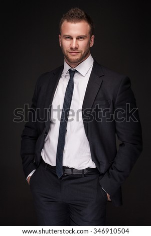 Portrait of young businessman isolated on dark background