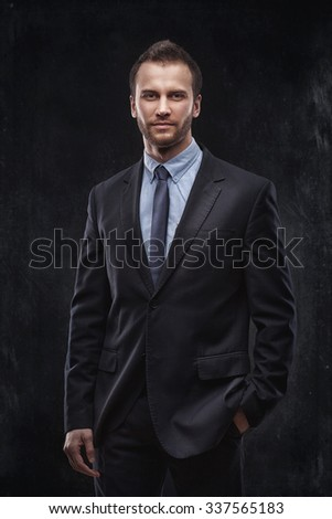 Portrait of young businessman isolated over dark background