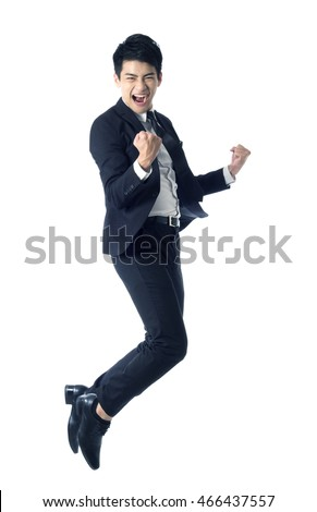 Portrait of young businessman jumping in the air and celebrating his success
