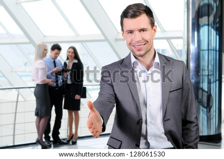 Portrait of young businessman looking at camera in working environment - stock photo