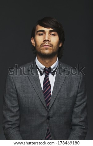 Portrait of young businessman looking at camera. Male business executive in suit isolated on black background. - stock photo