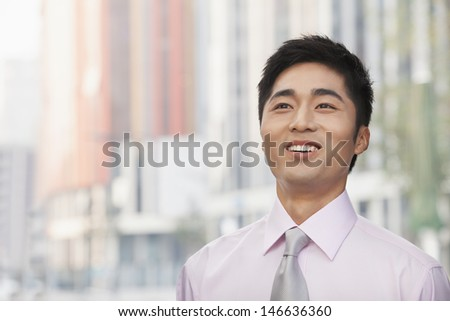 Portrait of young businessman, looking up - stock photo
