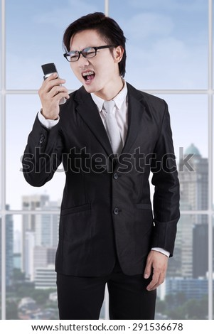 Portrait of young businessman looks angry and shouting on his cellphone