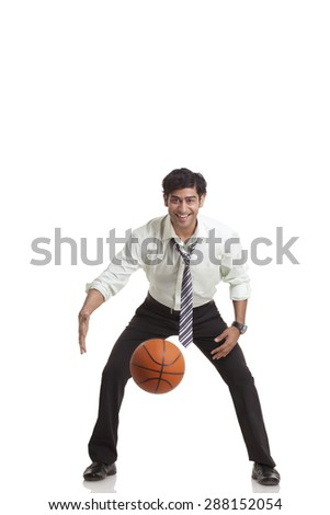 Portrait of young businessman playing basketball - stock photo