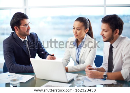 Portrait of young businessman presenting new project in laptop to his coleagues in office - stock photo
