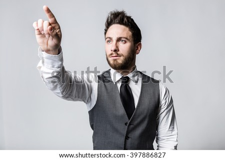 Portrait of young businessman pressing a button on an imaginary screen.