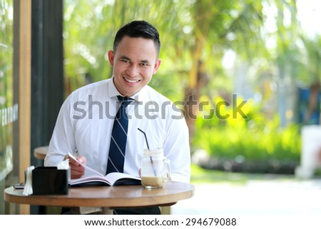 portrait of young businessman reading a book during coffee break with copy space