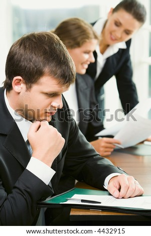 Portrait of young businessman reading an interesting agreement lying on the table