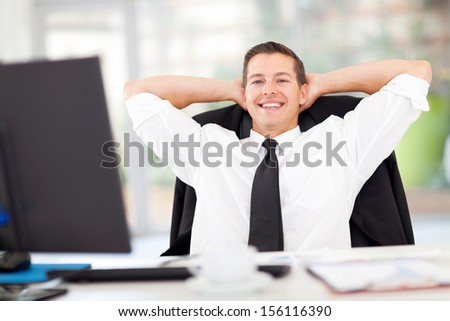 portrait of young businessman relaxed in office - stock photo