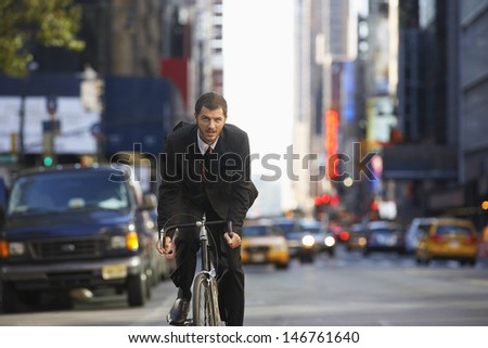 Portrait of young businessman riding bicycle to work on urban street - stock photo