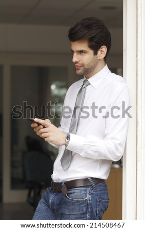 Portrait of young businessman sending text on mobile, while standing at office. Business person.