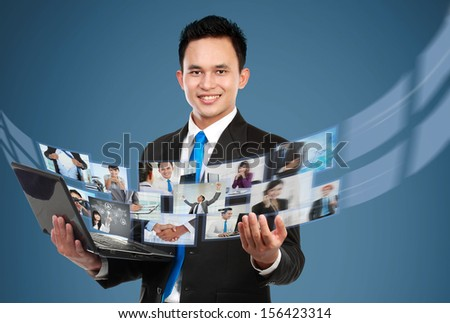 Portrait of young businessman sharing his photo and video files using laptop - stock photo