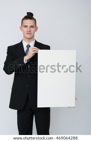 Portrait of young businessman showing blank signboard, with copyspace area for text or slogan, against grey background
