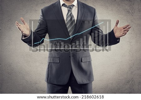 Portrait of young businessman showing flow chart of economic growth on the screen. Male entrepreneur with financial diagram posing in studio.  - stock photo