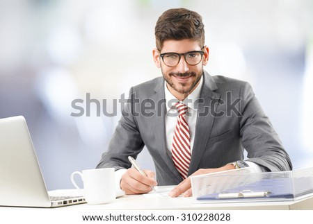 Portrait of young businessman sitting at desk in front of computer while writing and working on financial plan.