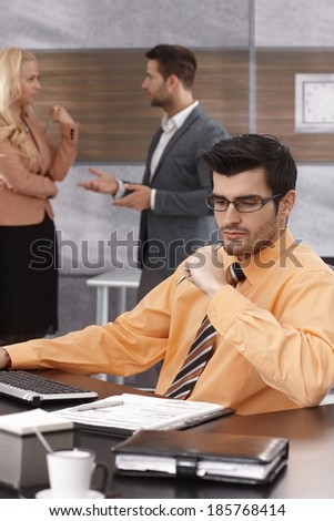 Portrait of young businessman sitting at desk, working.