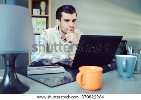 Portrait of young businessman sitting at desk, working with computer. - stock photo