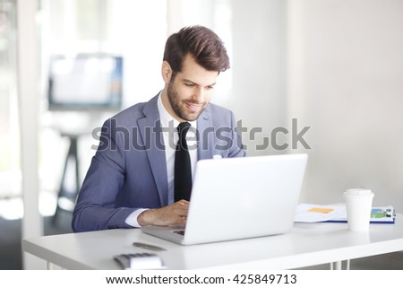 Portrait of young businessman sitting at office and typing on laptop while working on business presentation.