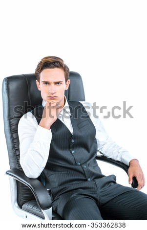Portrait of young businessman sitting in bossy chair on white background and looking at camera
