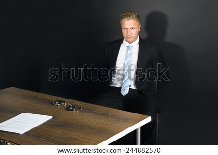 Portrait Of Young Businessman Sitting In Interrogation Room - stock photo