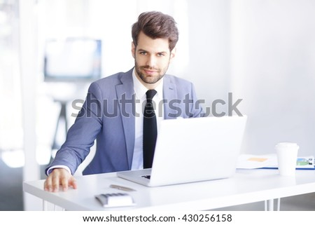Portrait of young businessman sitting in the office and using his laptop while working on new project.