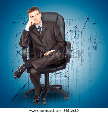Portrait of young businessman sitting on chair against graph background