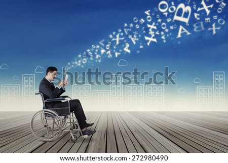 Portrait of young businessman sitting on wheelchair using a digital tablet to send message - stock photo