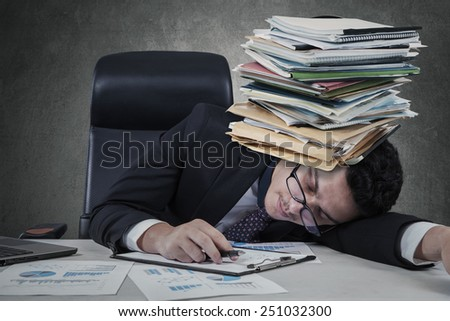 Portrait of young businessman sleeping with paperwork on his head - stock photo