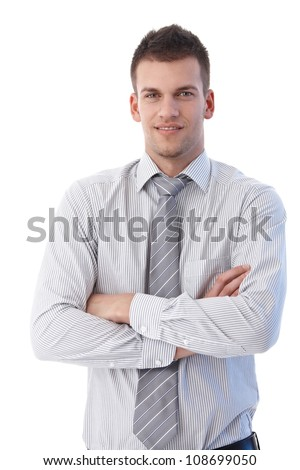 Portrait of young businessman standing arms crossed. - stock photo