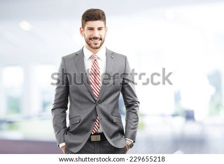 Portrait of young businessman standing at office. Business people. - stock photo