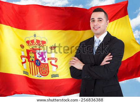 Portrait Of Young Businessman Standing In Front Of Spanish Flag