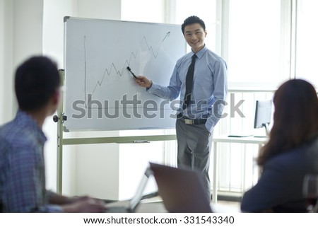 Portrait of young businessman standing in front of the whiteboard,holding marker pen,businessman and businesswoman sitting,having meeting in office - stock photo