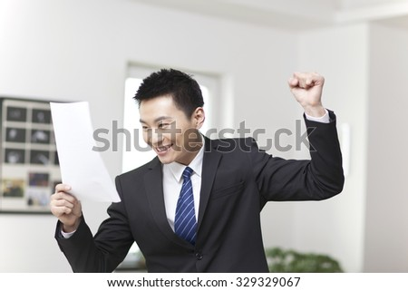 Portrait of young businessman standing,looking documents and holding list up