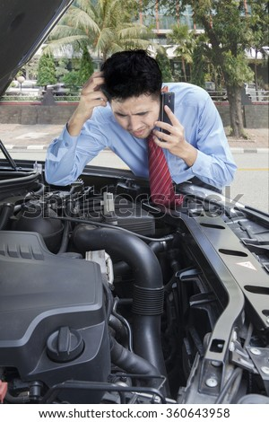 Portrait of young businessman talking on the phone while checking the broken machine car - stock photo