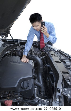 Portrait of young businessman talking on the phone while checking the broken machine car, isolated on white - stock photo