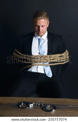 Portrait Of Young Businessman Tied With Rope Sitting In Front Of Table With Handcuff Placed On It - stock photo
